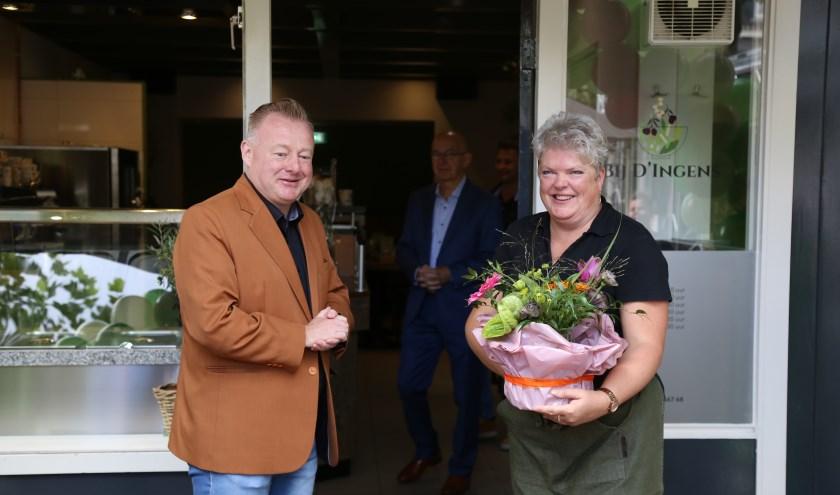 Ingrid van Veen neemt uit handen van wethouder Eric van den Broek een felicitatiegeschenk in ontvangst bij de opening van haar nieuwe zaak aan de Markt in Boxtel.   | Fotonummer: f3b606