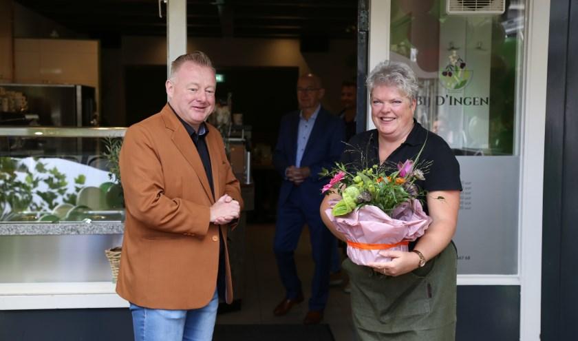 Ingrid van Veen neemt uit handen van wethouder Eric van den Broek een felicitatiegeschenk in ontvangst bij de opening van haar nieuwe zaak aan de Markt in Boxtel.   | Fotonummer: f7e423