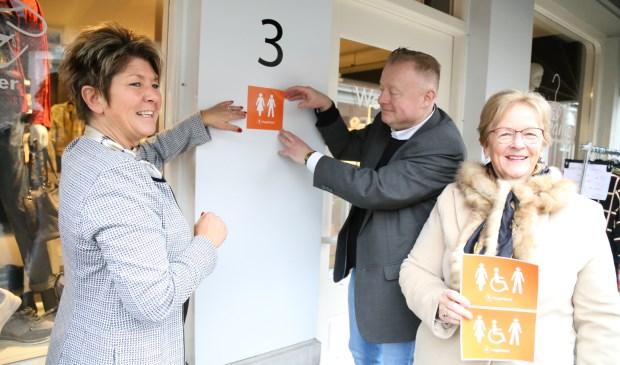 Ondernemer Petra Essen (l.), wethouder Eric van den Broek en Diny Stolvoort plakken de eerste 'Hoge Nood' sticker. Foto: Sander van Kasteren © MooiBoxtel