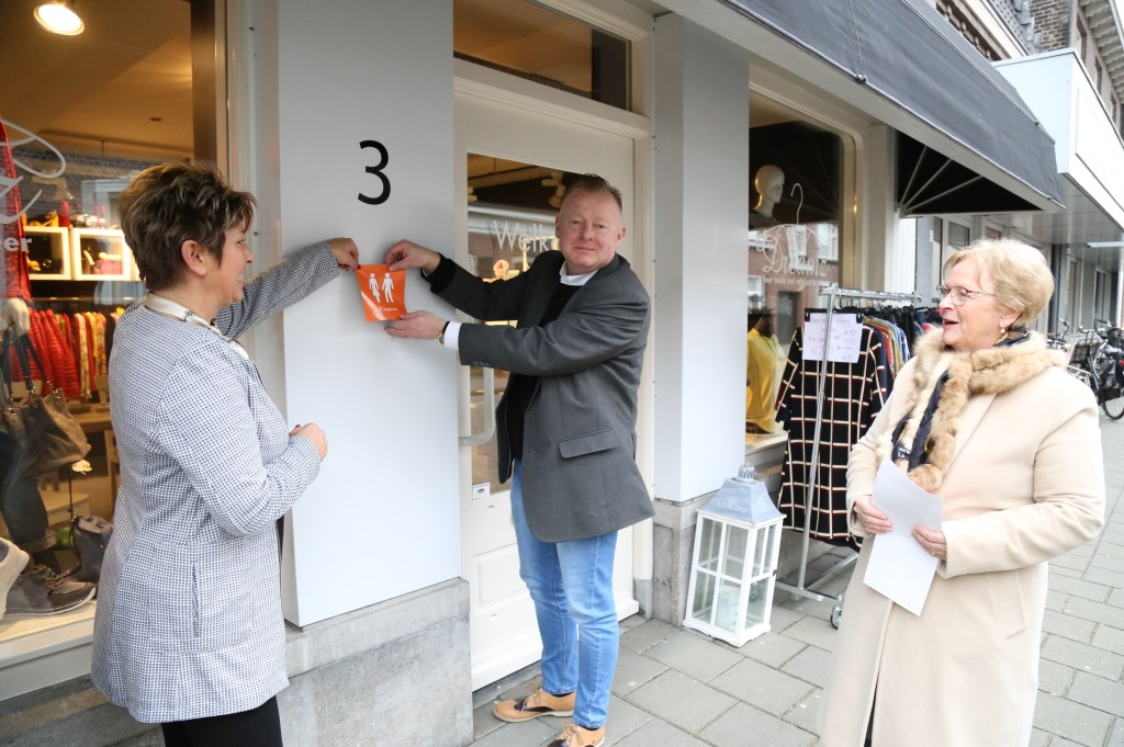 Ondernemer Petra Essen (l.), wethouder Eric van den Broek en Diny Stolvoort plakken de eerste 'Hoge Nood' sticker.    Fotonummer: b55bf9