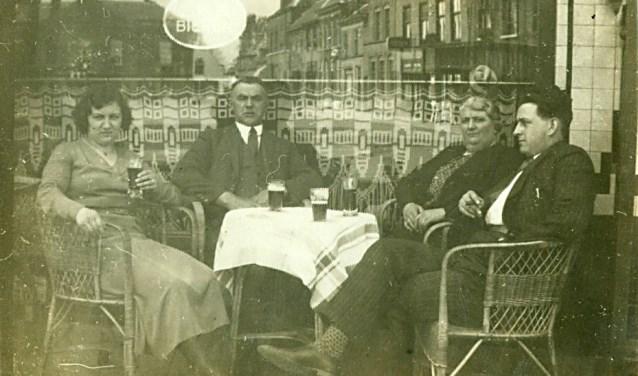 Een straatfotograaf op de Markt fotografeerde mensen die naar de Sint Petruskerk gingen of er vandaan kwamen. In de spiegeling in de etalage is oostkant van de Markt te zien (spiegelbeeld) en op de achtergrond het oude gemeentehuis dat in 1937 werd afgebroken Op de foto: Fam. Adam en Ru Verbruggen.     Fotonummer: abfffc