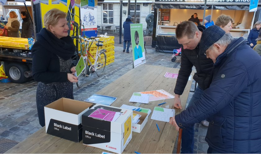 Mariëlle van Alphen probeert op de weekmarkt zoveel mogelijk Boxtelaren te enthousiasmeren voor het invullen van de enquête.   | Fotonummer: ab2726