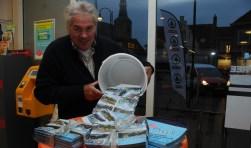 Piet Groffen van de Dorpstafel leegt de emmer met kaarten bij de Spar.