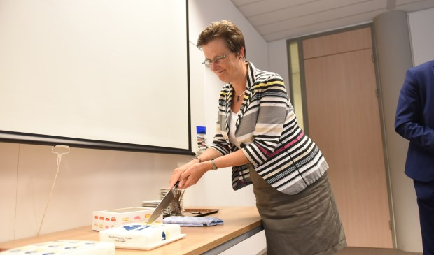 Burgemeester Ger van de Velde snijdt de taart omdat Tholen als 250e gemeente aan het project meedoet.