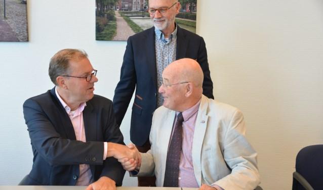 Voorzitter Jan Legierse (rechts) en wethouder Koos Krook bezegelen de overeenkomst met een handdruk. Penniingmeester Rien van Zundert kijkt toe.