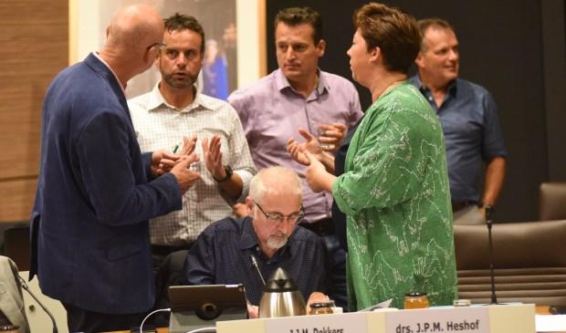 Beeld uit de bewuste raadsvergadering. Raadsleden van CDA, VVD en Pvda/GL in gesprek over de motie over de regenboogvlag. Jacques Dekkers (zittend) diende die in.
