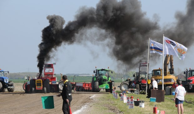 Zwarte rook kleurt de lucht boven het terrein van de trekkertrek.