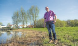 Ondernemer André van Ast met rechts het Stallands bos en achterin het chaletpark en links de plas die hij wil omvormen tot forellenvijver.