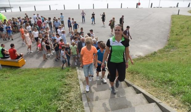Leerlingen van de twee scholen gezamenlijk openden vorige week twee wandelroutes in Sint Philipsland. Vooraan Roseline van den Heuvel. Ze woont in Sint-Annaland, maar bekommert zich nog wel om haar geboortedorp.