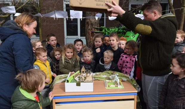 De kinderen kijken naar de zojuist onthulde maquette. Links juf Elly Dongen en rechts juf Anne-Mieke Reedijk.