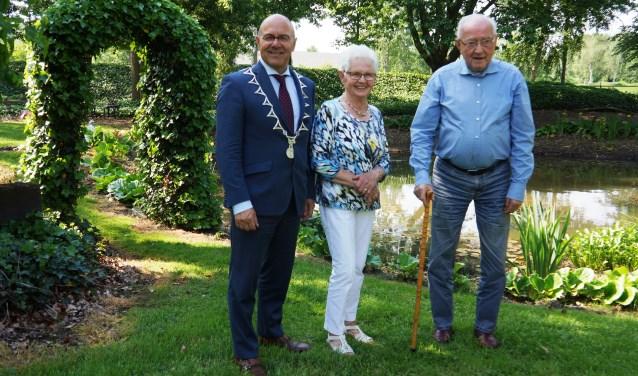 Riek en Theo van Genugten staan met burgemeester Van Rooij bij hun mooie vijver  | Fotonummer: c11174