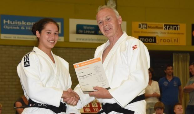 Dewi Lo-a-Njoe ontvangt uit handen van Cor van der Heijden het diploma dat bij haar tweede dan hoort  | Fotonummer: 6874a4