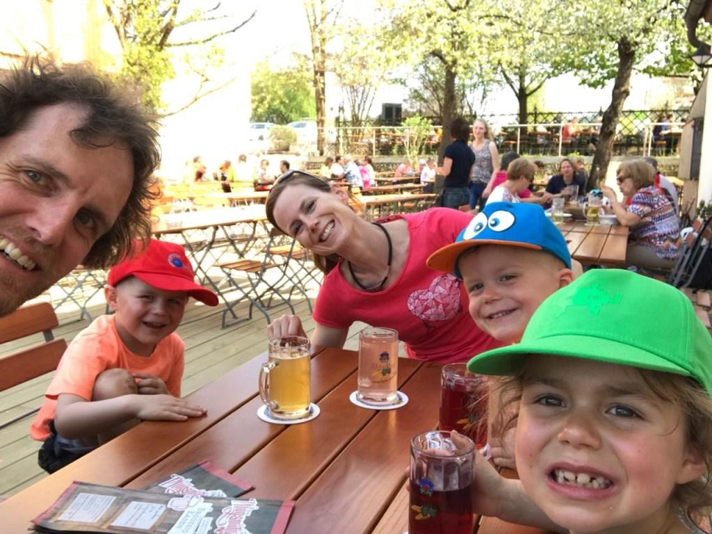 Janneke met haar vriend en de kinderen in een Biergarten.  © MooiRooi