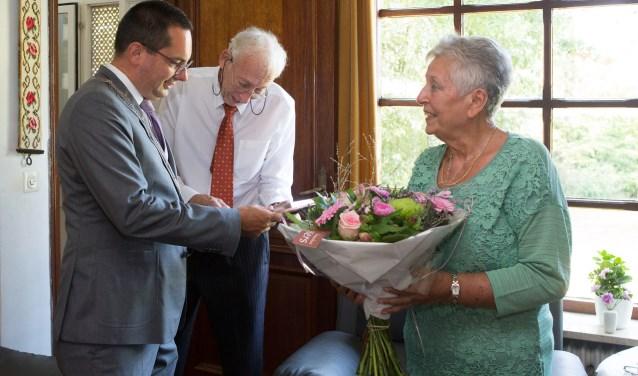 Een bloemetje en een kopie van de trouwakte voor het briljanten bruidspaar Corbet-Verhoeven.