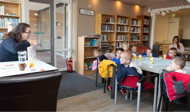 Laurianne Verhagen leest schoolkinderen voor in de bieb van 't Blickvelt.