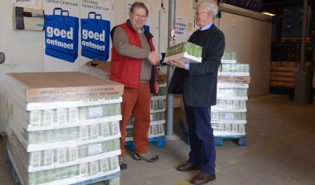 Martien Franken (rechts) overhandigt de koffie aan Jan den Ridder (links) van de Voedselbank.