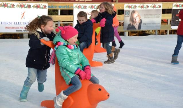 De kinderen vermaken zich grandioos met én op de schaatshulpen.