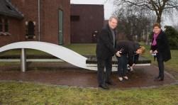 Initiatiefneemster Loes Kools (midden) bevestigt samen met raadsleden Adri Gelten en Adri van Zweden een borstel onder een van de bankjes.