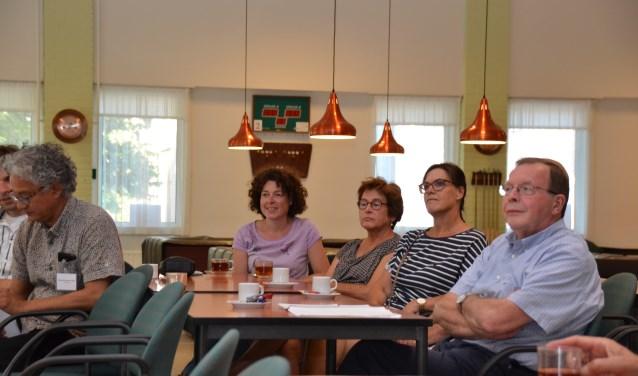 Bezoekers van de inloopavond over windmolens luisteren naar de uitleg van wethouder Andrew Harijgens.