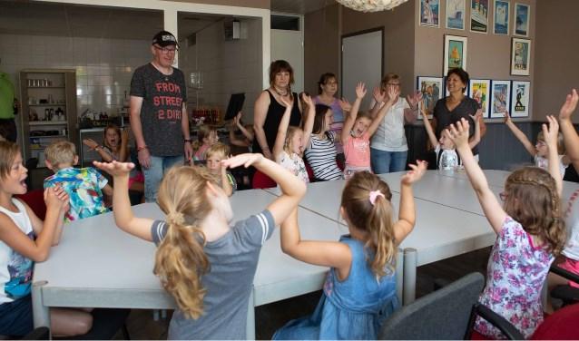 Kinderen van de plaatselijke basisschool hebben plezier bij de opening van het Participatiecafé.