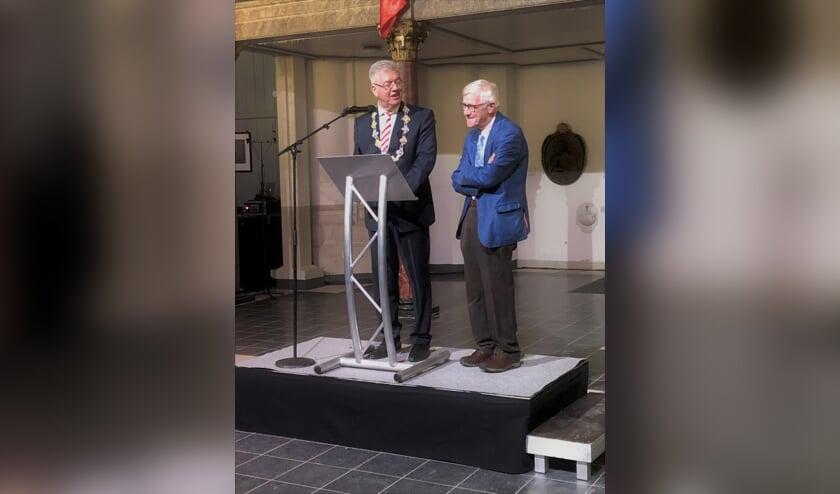 De heer Ferd Quik (rechts) ontvangt de erepenning met inscriptie van gemeente Bergen op Zoom uit handen van burgemeester dr. Frank Petter.