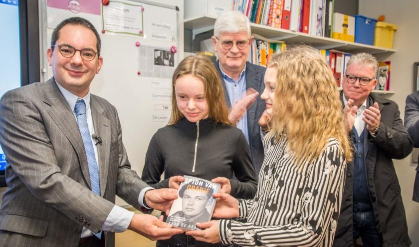 Burgemeester Adriaansen overhandigt het boek 'Spion van Oranje' aan Britt en Loïs.