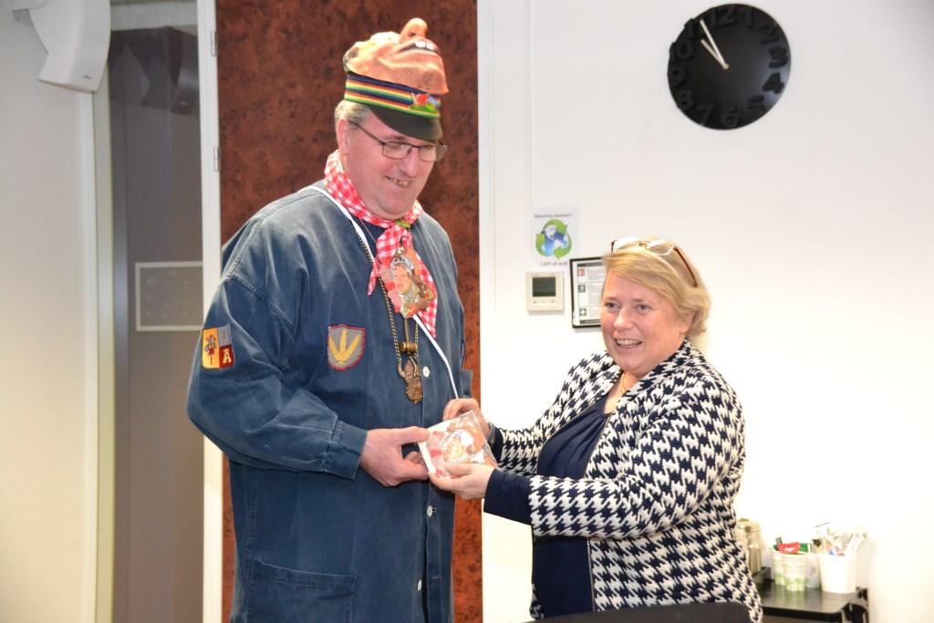 Voorzitter Stichting Alterse Carnaval John van Tilburg overhandigt het insigne aan wethouder Annette Stinenbosch.  © Minerve Pers