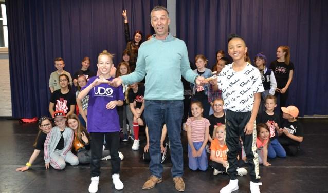 Muzikant Ben van Hoof overhandigt het sponsorbedrag aan dansers van House of Marqeez.