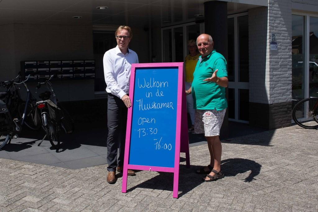 Wethouder Lars van der Beek en dhr. Adriaansen openden de nieuwe huiskamer door het welkom-bord buiten te plaatsen.  © Minerve Pers