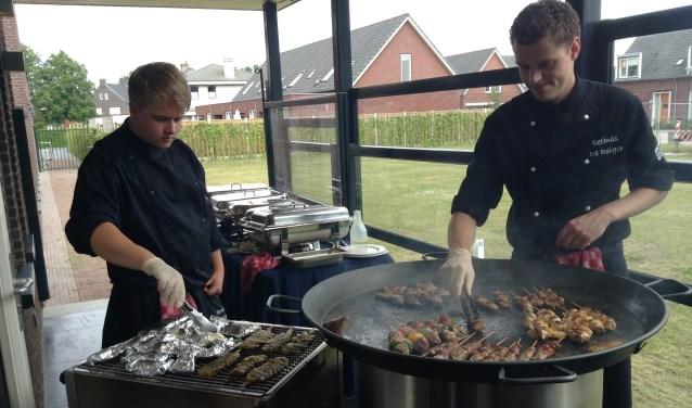 Mike Versantvoort (rechts) achter de barbecue.