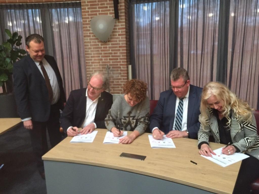 Staand: Eus Witlox. Zittend: Sikko Oegema (PvdA), Janine Heisterkamp (TEAM),  Johan van Gerwen (CDA) en Wilma Wagenaars-Van Beers tekenen het akkoord.  © Kliknieuws Veghel