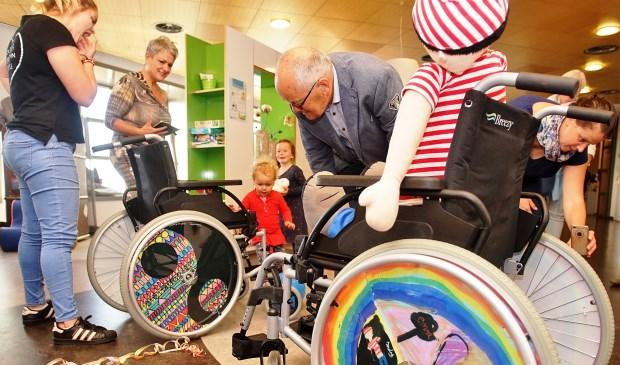 Jan van Raaij van Vrienden van het Maasziekenhuis kijkt goedkeurend naar een gepimpte rolstoel.