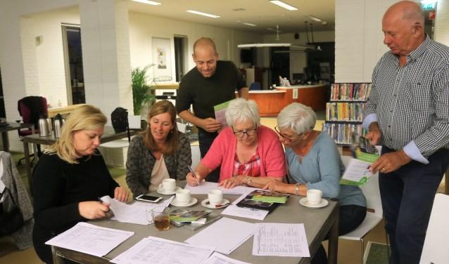 Marion Vermeulen (tweede van links) en Wout Mulders van Mooiland (staande in het midden) helpen planten selecteren voor geveltuinen.