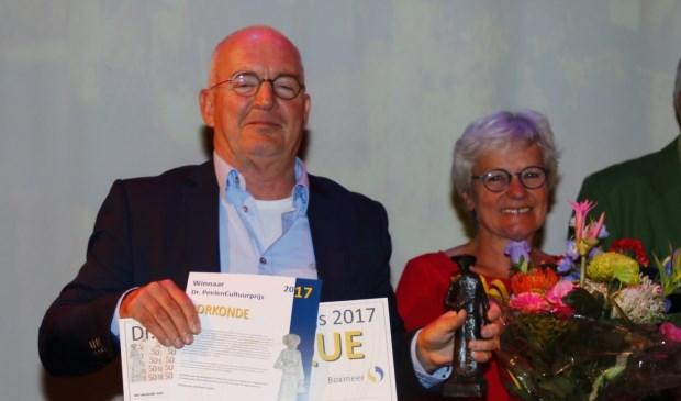 Cultuurprijswinnaar Henk van Os met de oorkonde en het Dr. Peelenbeeldje.