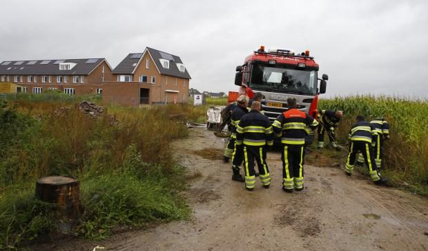 Brandweermannen werpen rondom de vrachtwagen een zanddijkje op. Foto: SK-Media