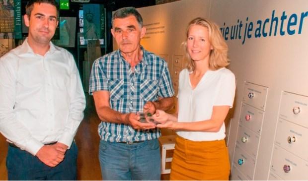 Jan Kusters en drs. Lenie van Esser, projectleider presentaties van het Stedelijk Leiden, met de muntschat. Links Felix van Ballegooij van de gemeente Sint Anthonis.