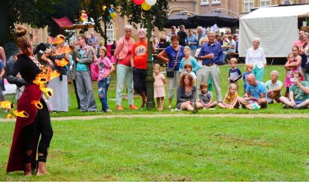 Toeschouwers kijken vol bewondering naar een jongleuse met vuur tijdens Kunstival van vorig jaar.