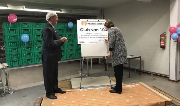 Burgemeester Wobine Buijs van Oss tekent als eerste lid van de Club van 100 van de Voedselbank voor Oss en Omgeving haar overeenkomst. Links haar voorganger Herman Klitsie.