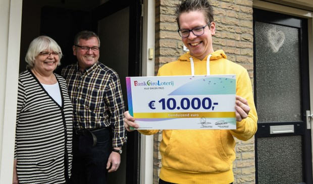 Gert Jan uit Geffen ontvangt, in het bijzijn van zijn ouders, een cheque van 10.000 euro van de BankGiro Loterij.