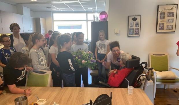 De leerlingen overhandigen de bloemen aan een bewoonster.