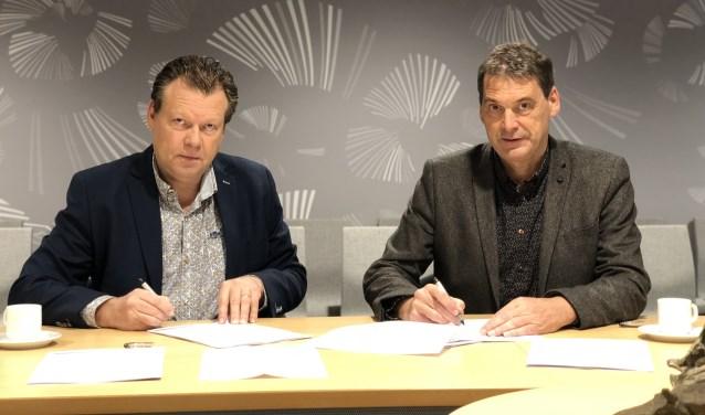 Eus Witlox en Jan van Vucht ondertekenen de contracten.
