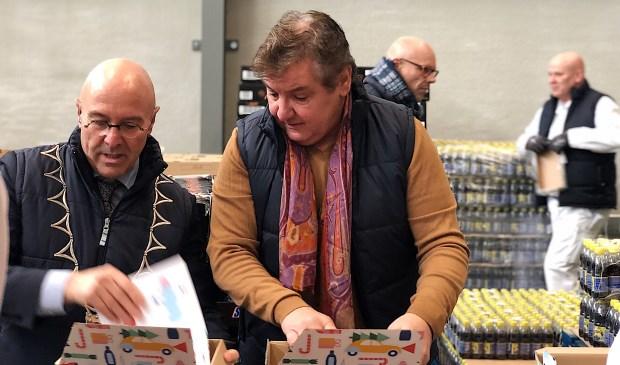 Burgemeester Van Rooij en René Froger zijn druk bezig met het inpakken van de voedselpakketten.   © Kliknieuws Veghel