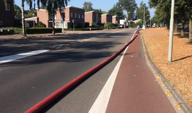 De brandslang die over de weg lag