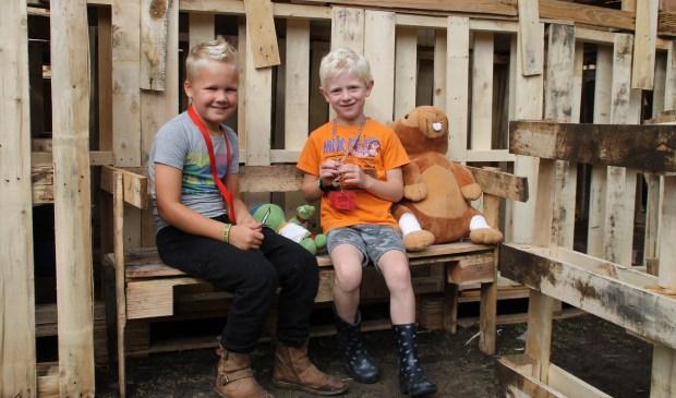 Pim (7) en Jens (6) zitten even op een bankje bij te praten.
