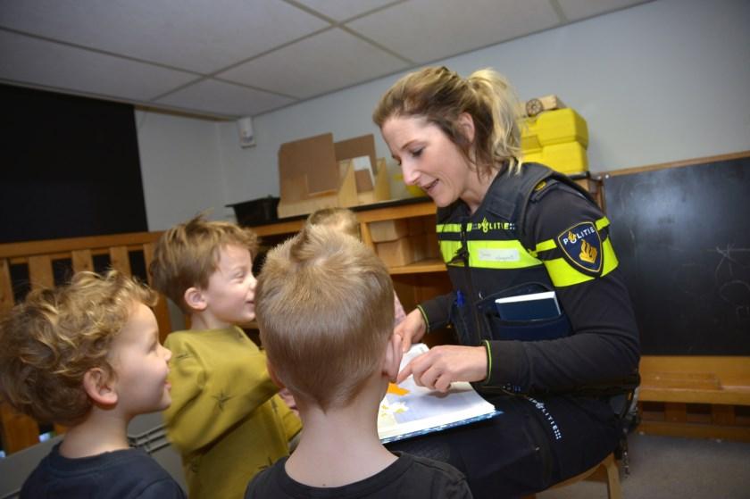 Met lachende gezichtjes luisteren de kinderen naar de wijkagente
