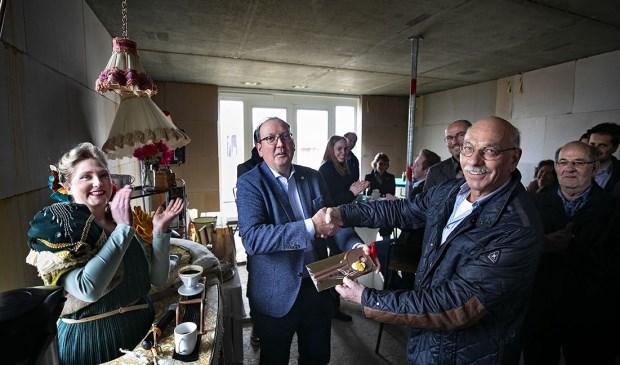 Wethouder Van den Bogaard (L) overhandigt aan een toekomstige bewoner de 'huissleutel'.