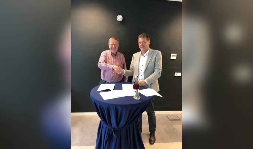 Voorzitter Riny van Dijk van de Bewonersraad van Area (links) tekent samen met directeur-bestuurder Jan van Vucht van Area het lokaal huurakkoord