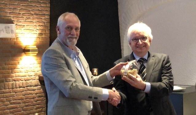 Theo van Brunschot (links) overhandigt burgemeester Gradisen het eerste pakje Moockse Raampjes. (foto: Jos Gröniger)