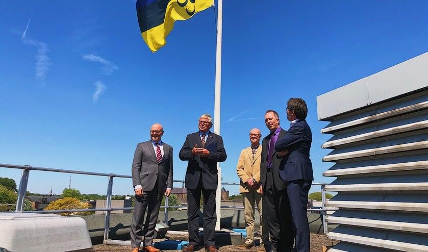 De nieuwe vlag wappert boven de hoofdrolspelers van afgelopen woensdag. Ook burgemeester Kees van Rooij (uiterst links) was aanwezig.