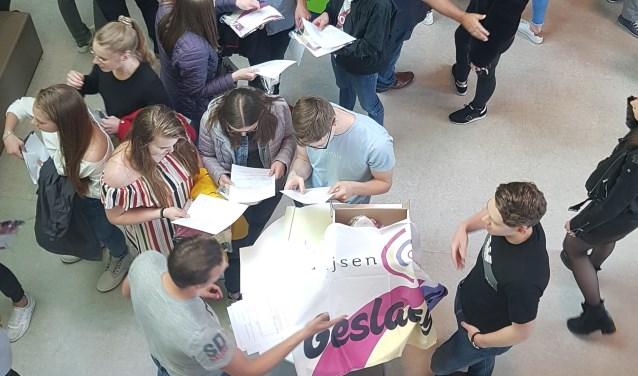 De Zwijsen-leerlingen nemen elkaars cijferlijsten door.